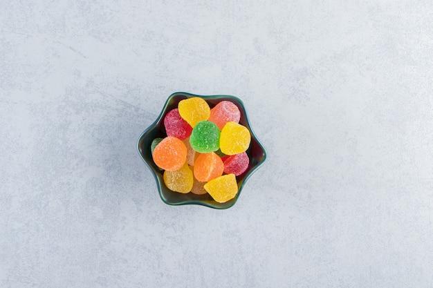 대리석에 다채로운 젤리 마멀레이드의 검은 그릇.