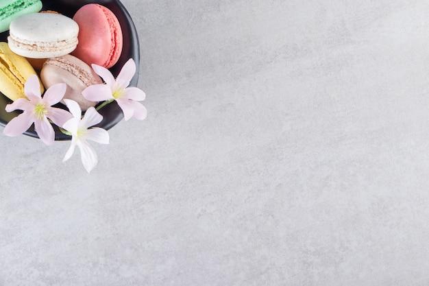 石の背景に花とカラフルな甘いマカロンの黒いボウル。