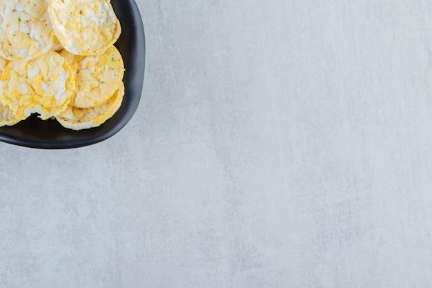 Черная чаша вкусных рисовых чипсов на камне.