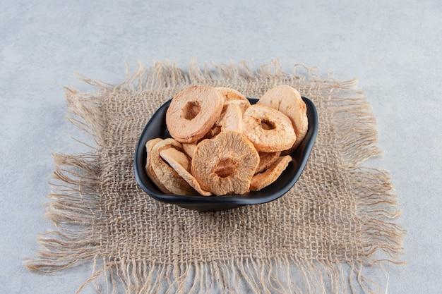 Черная миска здоровых сушеных яблочных колец на каменном фоне
