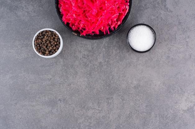 石のテーブルに赤キャベツのピクルスの黒いボウル。
