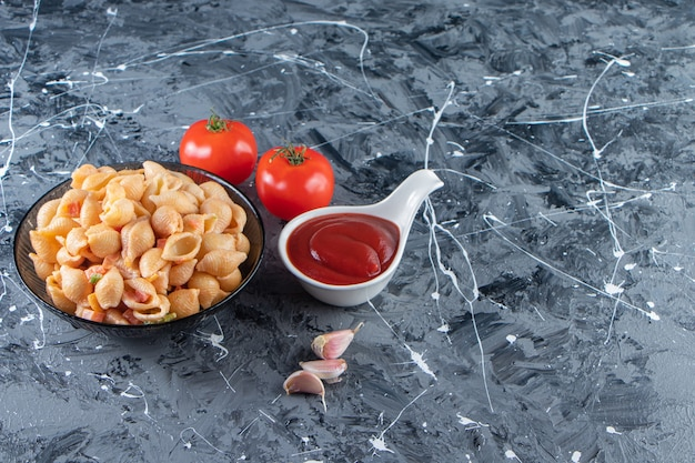 대리석 표면에 케첩을 넣은 맛있는 조개 파스타의 검은 그릇.