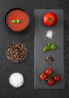 Black bowl plate of creamy tomato soup on black table with stone chopping board and raw tomatoes, pepper and salt. top view.
