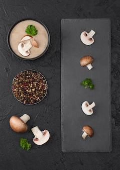 黒の石板と新鮮なキノコと黒の背景にクリーミーな栗のシャンピニオンマッシュルームスープの黒のボウルプレート。