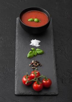 石のチョッピングボードと生のトマト、コショウ、塩と黒いテーブルの上のクリーミーなトマトスープの黒いボウルプレート。上面図。