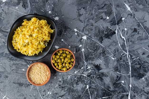 Black bowl of saffron rice and green peas on marble background.
