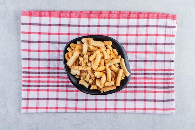 Ciotola nera di gustosi cracker croccanti su sfondo di pietra.