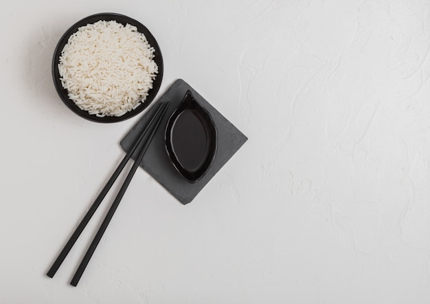 Black bowl with boiled organic basmati jasmine rice with black chopsticks