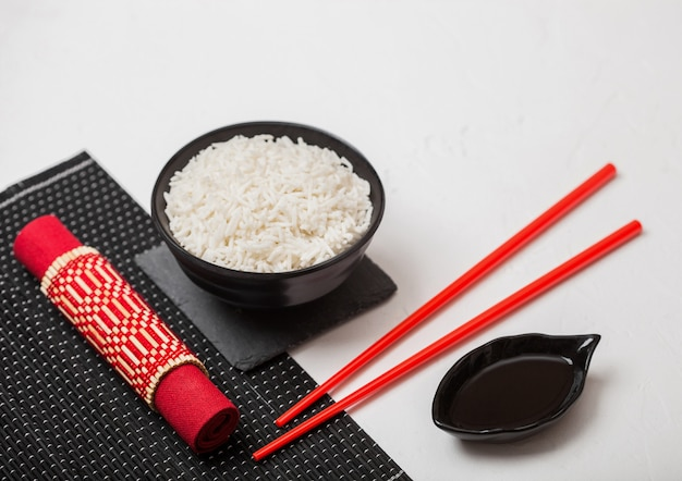Black bowl with boiled organic basmati jasmine rice with red chopsticks and sweet soy sauce