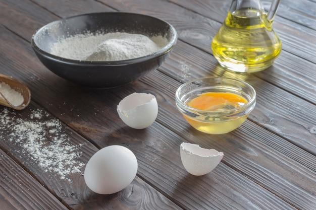 밀가루와 검은 그릇. 버터, 계란, 밀가루와 나무 숟가락과 유리 병.