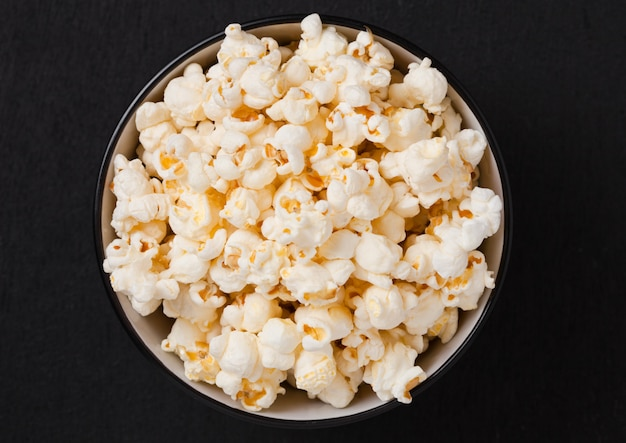 Black bowl with fresh salted popcorn on wooden background
