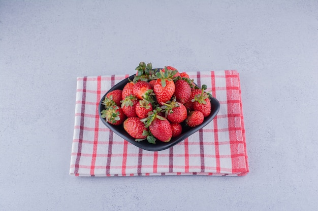 Black bowl with a heap of strawberries on marble background.