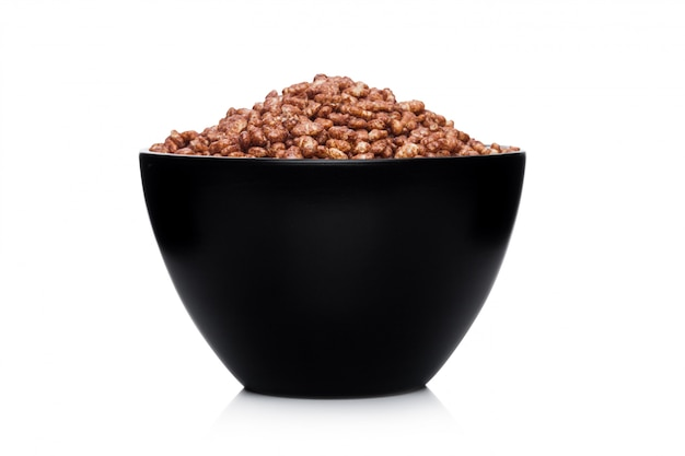 Black bowl with natural organic granola cereal chocolate flakes on white