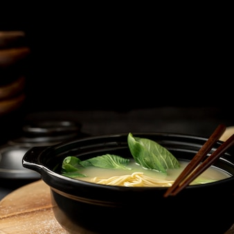 Black bowl with noodle soup on a black background
