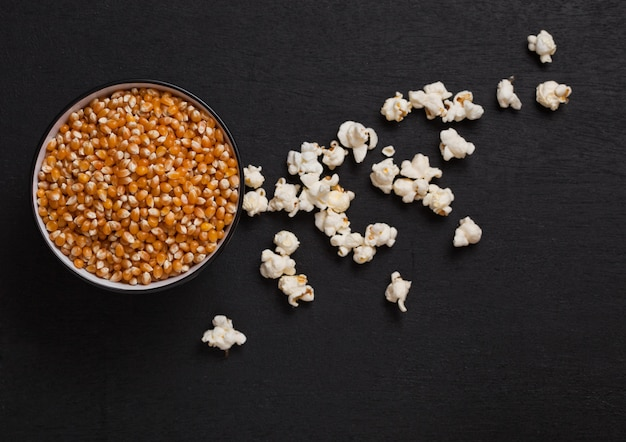 Black bowl with raw sweet corn and popcorn on black wooden background