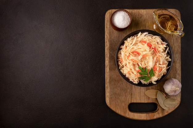 Black bowl with sour sauerkraut  on wooden cutting board on dark background flat lay with copy space
