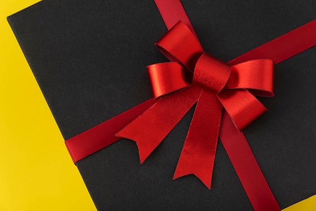 Черный ящик с красным бантом крупным планом. элегантный подарок.