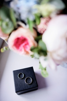 Black box with wedding rings stands under a pink bouquet