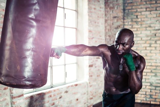 ジムで重い袋をパンチする黒のボクサー