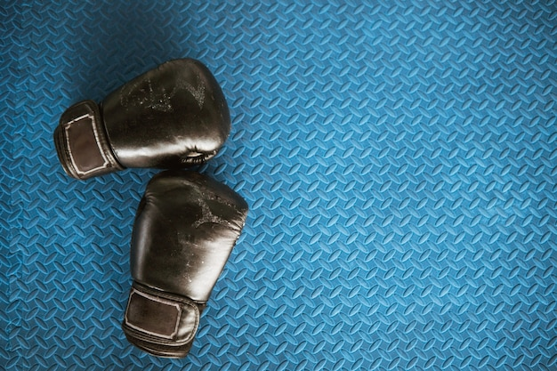 Black boxing gloves on blue iron flooring at boxing camp