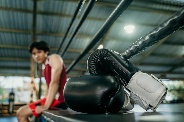 ジムのボクシングリングの黒いボクシンググローブ。トレーニング用スポーツ用品