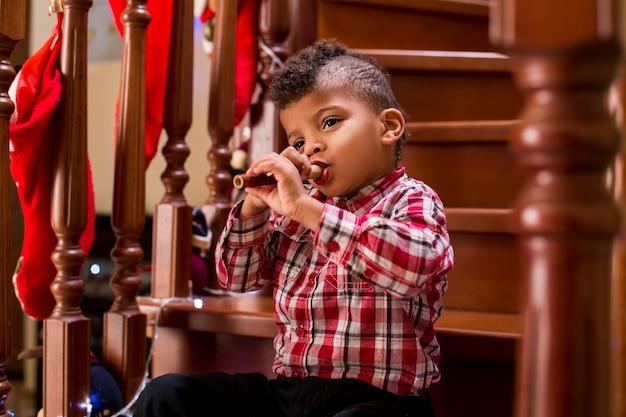 Черный мальчик играет на флейте ребенок играет на флейте на лестнице, у вас должно быть мастерство, можете ли вы произвести впечатление на публику