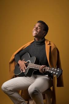 黒い男の子がギターを弾く