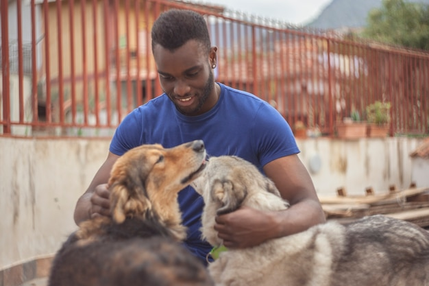 Черный мальчик от счастья играет с собаками
