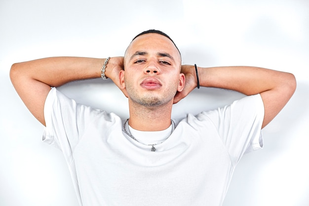 Black boy with hand behind head on white background, studio shoot