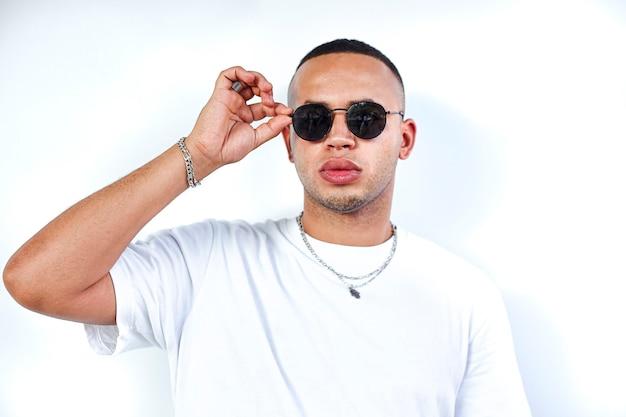 Black boy with hand on sunglasses on white background studio shoot