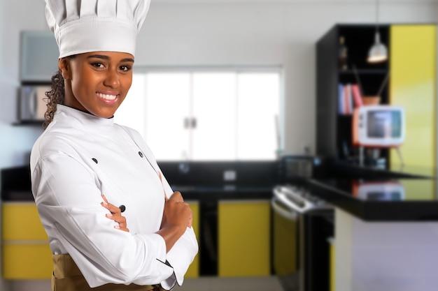 흑인 브라질 여자 요리사 요리 공간에서 흐리게 부엌 카메라를보고.