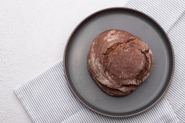 Черный хлеб домашний пирог. черный хлеб посыпать мукой. свежеиспеченный домашний ремесленный ржаной и хлеб из белой муки. вид сверху.