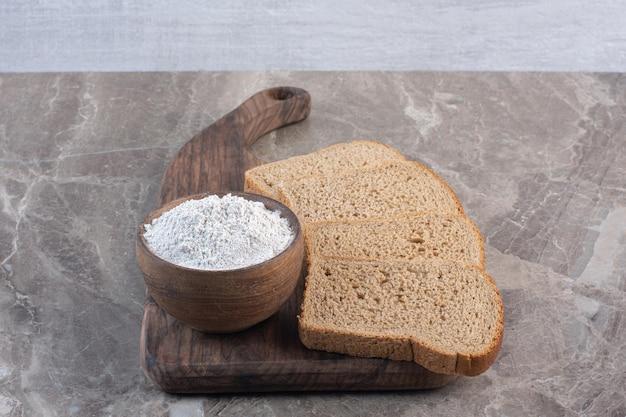大理石の背景のボード上の黒いパンのスライスと小麦粉のボウル。高品質の写真