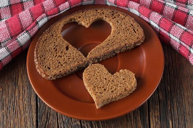Ломтики черного хлеба и кусок в форме сердца на деревенском столе