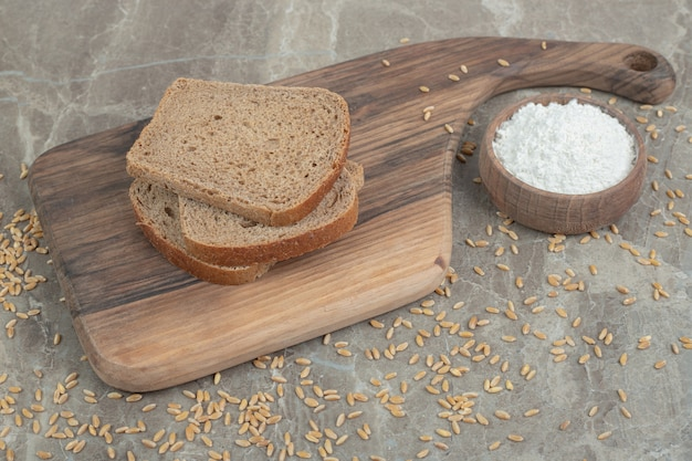 Black bread slices and bowl of flour on marble surface. high quality photo
