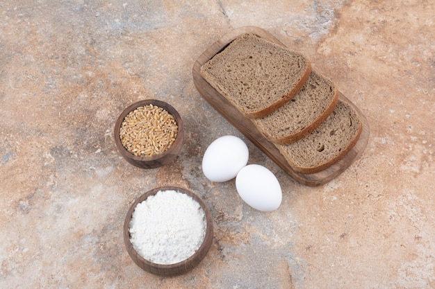 Black bread slices, flour, barley and eggs on marble surface