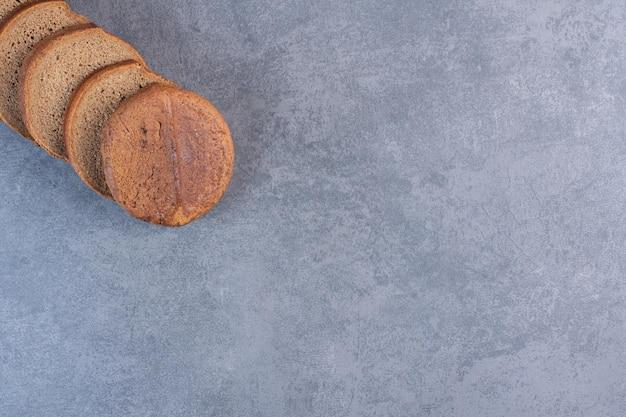 Ломтики черного хлеба выстроились на мраморном фоне. фото высокого качества