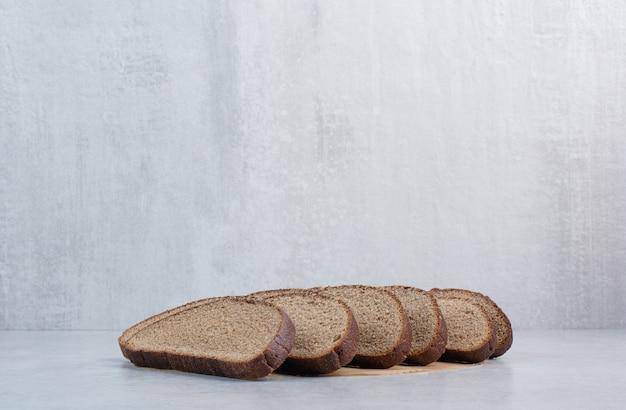 대리석 배경에 검은 빵 조각. 고품질 사진