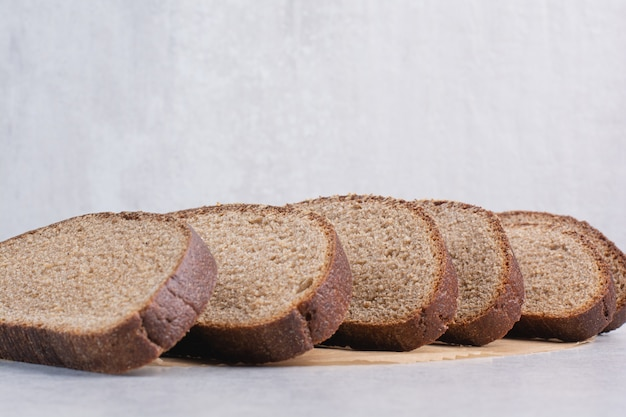 Ломтики черного хлеба на каменной поверхности