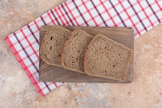Ломтики черного хлеба на деревянной доске со скатертью