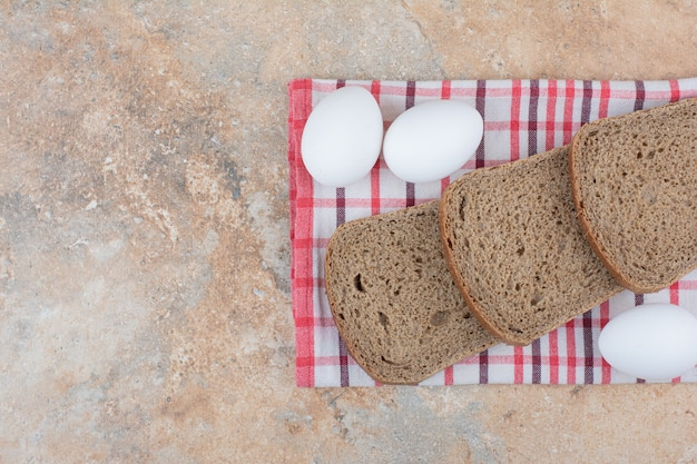 Black bread slices on tablecloth with eggs