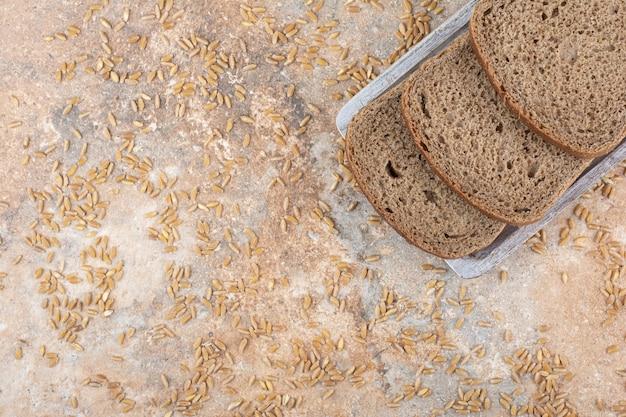 Fette di pane nero con chicchi d'orzo su superficie in marmo
