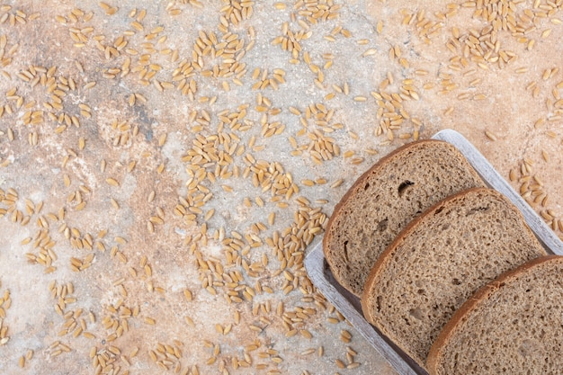 Black bread slices with barley grains on marble surface