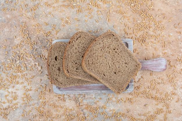 Ломтики черного хлеба с зернами ячменя на мраморной поверхности