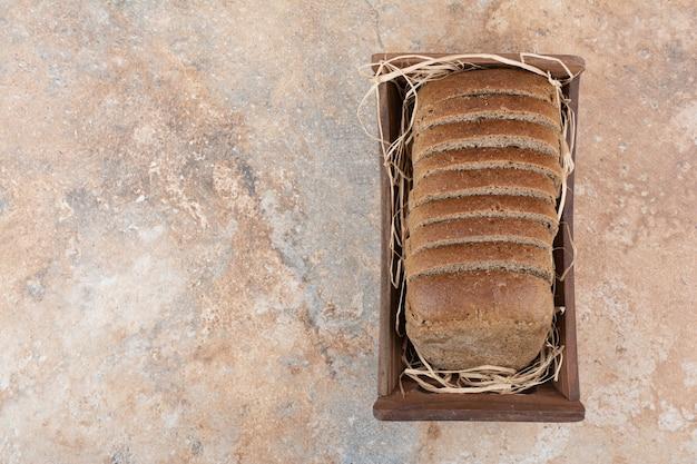 Black bread slices in wooden bowl