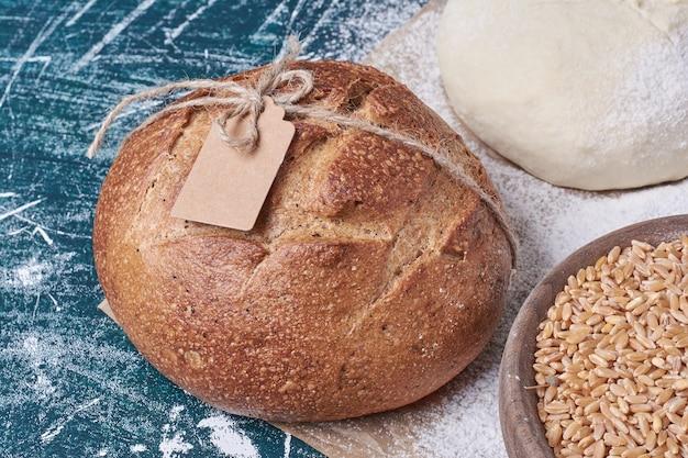Pane nero sui chicchi di grano sulla tavola blu.