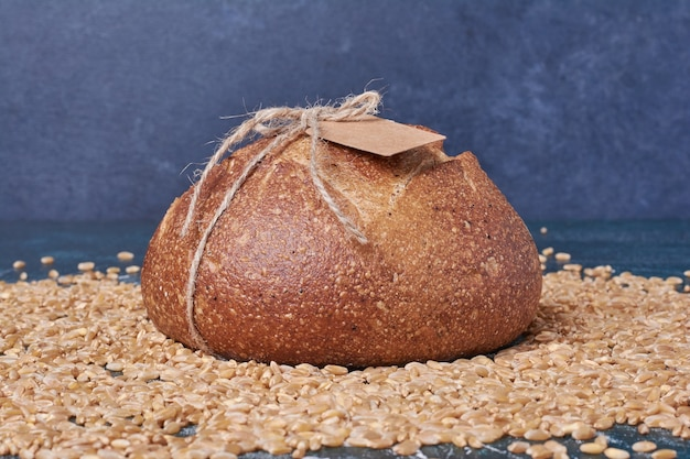Black bread on wheat grains on blue table.