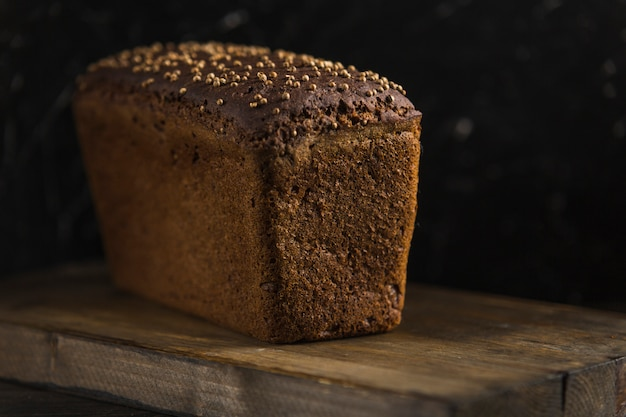 Black bread with caraway seeds on wooden board