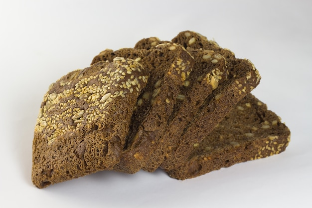 Black bread with sunflower seeds and sesame seeds on a white background
