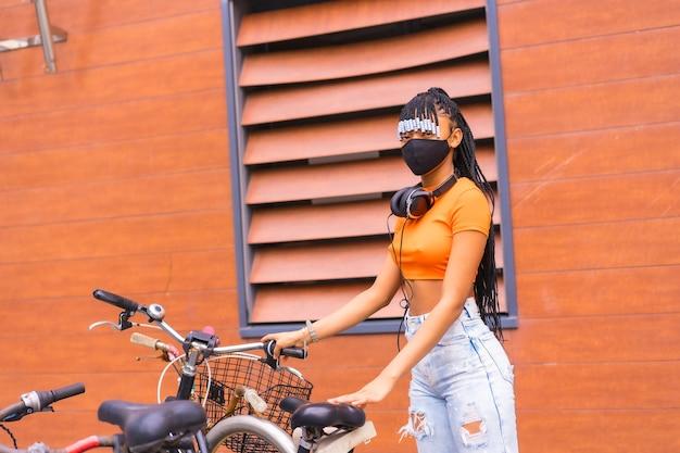 コロナウイルスパンデミックによるマスクを持つ黒人の品種の少女、市内のオレンジ色のシャツを着たアフリカの民族グループ。市内に駐車した自転車のコーフィング